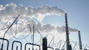 Taggtråd som ett symbol av mänsklighet i gisslan av prorgess förorening för fabrik för luftbakgrund blå Global uppvärmningproblem lager videofilmer