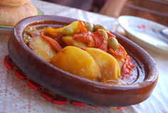 Tagine. Typical Moroccan food with potatoes, tomatoes and olives served with traditional bread Royalty Free Stock Photo