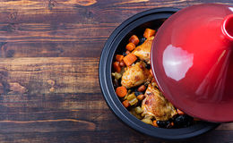 Tagine with cooked chicken and vegetables. Traditional moroccan cuisine. Wooden background Royalty Free Stock Photography