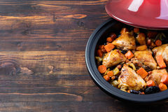 Tagine with cooked chicken and vegetables Wooden background Copy space Royalty Free Stock Photos