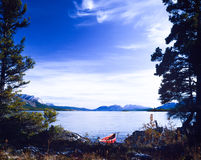 Tagish Lake Yukon Canada red canoe wilderness trip. Red canoe on boreal forest taiga wilderness shore of beautiful calm Tagish Lake, Yukon Territory, Canada Royalty Free Stock Image