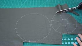 Tagli dell'artigiano un dettaglio del sacchetto da cuoio con le forbici stock footage