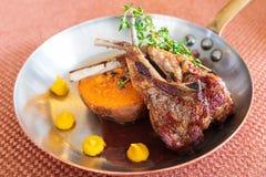 Tagli di agnello arrostiti della Nuova Zelanda con le patate dolci arrostite, salsa naturale condita con le erbe fotografia stock libera da diritti