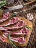 Tagli di agnello crudi con aglio e le erbe immagini stock