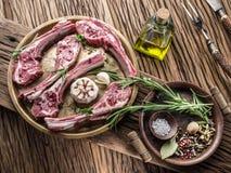 Tagli di agnello crudi con aglio e le erbe fotografia stock libera da diritti