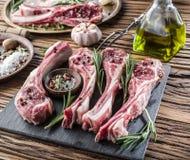 Tagli di agnello crudi con aglio e le erbe fotografia stock