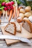 Tagli di recente il pane sul tagliere con le verdure organiche Immagine Stock Libera da Diritti