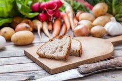 Tagli di recente il pane sul tagliere con le verdure organiche Fotografia Stock Libera da Diritti