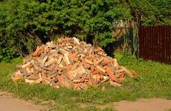 Tagli e spacchi la legna da ardere impilata in un mucchio vicino alla casa Fotografia Stock