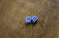Tagli i cubi a cubetti sui sixes di legno di una tabella due fotografie stock
