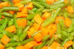 Tagli i fagioli asparagi ed ha tagliato la carota a cubetti Fotografie Stock Libere da Diritti