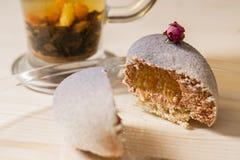 Tagli i muffin del dolce sotto forma di cuore con lo zucchero in polvere su un fondo di legno Tè verde della tazza Immagine Stock