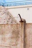 Tagli il filo spinato arrugginito sul recinto concreto Immagine Stock