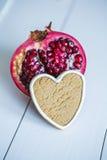Tagli il melograno e la carota sotto forma di cuore su una tavola bianca Immagini Stock Libere da Diritti