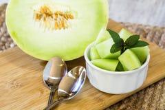 Tagli il melone di melata con menta piperita ed i cucchiai immagine stock libera da diritti