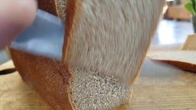 Tagli il pane con un coltello su un colpo lento di legno archivi video