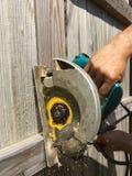 Tagli il recinto di legno con la sega elettrica Immagine Stock