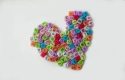 Tagli il simbolo a cubetti impilato del cuore su fondo bianco isolato Fotografia Stock
