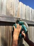 Tagli il vecchio recinto con la sega elettrica Fotografie Stock