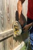 Tagli il vecchio recinto di legno con la sega elettrica Immagini Stock