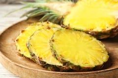 Tagli l'ananas succoso fresco sul vassoio di legno immagini stock