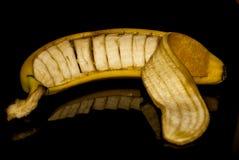 Tagli la banana in sua buccia fotografie stock