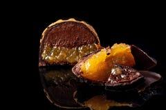 Tagli la caramella fatta a mano di lusso con cioccolato ed il confiture giallo che riempiono sul fondo nero Immagini Stock Libere da Diritti