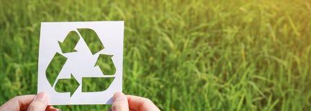 Tagli la carta con il logo del riciclaggio sopra l'erba verde Immagini Stock