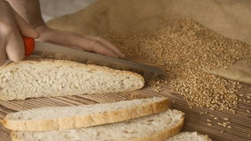Tagli la fetta di pane sulla tavola di legno, al rallentatore, vicino su stock footage