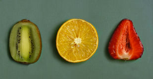 Tagli la frutta irritata - l'arancia, la fragola, kiwi sul bordo della cucina Immagine Stock