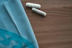 Tagli la gonna in tessuto blu, pezzo di plastica e due bobine di filo grigio su una tavola marrone dei tailor's Copyspace fotografia stock libera da diritti