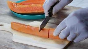 Tagli la papaia matura in pezzi stock footage