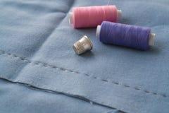 Tagli la parte della gonna con una pieghettatura cucita, il ditale e due bobine del filo Due bobine del rosa e dei fili e dello s fotografia stock