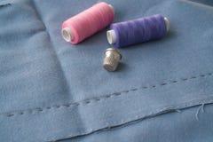 Tagli la parte della gonna con una pieghettatura cucita, il ditale e due bobine del filo Due bobine del rosa e dei fili e dello s fotografia stock libera da diritti