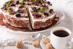 Tagli la torta di formaggio con i pezzi di biscotti e di caffè del cioccolato sulla t Fotografia Stock Libera da Diritti