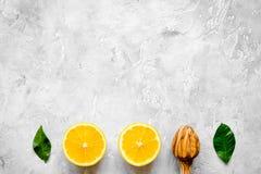 Tagli le arance e gli spremiagrumi di legno sulla vista superiore del fondo concreto Fotografia Stock Libera da Diritti