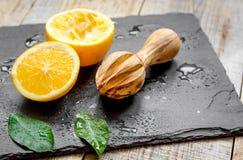 Tagli le arance a metà e gli spremiagrumi su fondo di legno Immagine Stock