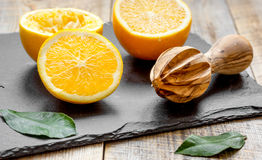 Tagli le arance a metà e gli spremiagrumi su fondo di legno Fotografia Stock