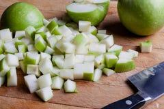 Tagli le mele verdi dal lato con il coltello Immagini Stock