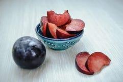 Tagli le prugne mature su un piatto Fotografie Stock
