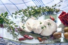 Tagli un pezzo della mozzarella con il timo dell'erba, i peperoncini rossi ed i pomodori seccati al sole in un panno leggero Cuci Fotografia Stock Libera da Diritti