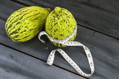 tagli un piccolo melone con un coltello, mangi un melone acerbo, piccoli meloni acerbi, Fotografia Stock