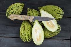 tagli un piccolo melone con un coltello, mangi un melone acerbo, piccoli meloni acerbi, Immagini Stock