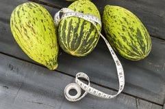 tagli un piccolo melone con un coltello, mangi un melone acerbo, piccoli meloni acerbi, Fotografia Stock Libera da Diritti