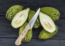tagli un piccolo melone con un coltello, mangi un melone acerbo, piccoli meloni acerbi, Immagini Stock Libere da Diritti