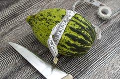 tagli un piccolo melone con un coltello, mangi un melone acerbo, piccoli meloni acerbi, Immagine Stock Libera da Diritti