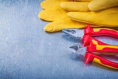 Tagliafili di cuoio delle pinze dei guanti di sicurezza su fondo metallico Immagini Stock Libere da Diritti