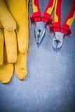 Tagliafili giallo delle pinze dei guanti protettivi sul backgrou metallico Immagini Stock