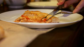 Tagliando e mangiando pizza italiana con carne, bacon stock footage