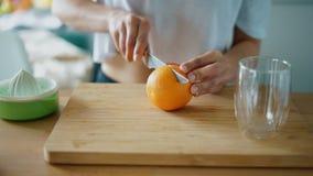 Tagliando frutta arancio per la spremuta del succo fresco Chiuda sulle mani femminili video d archivio